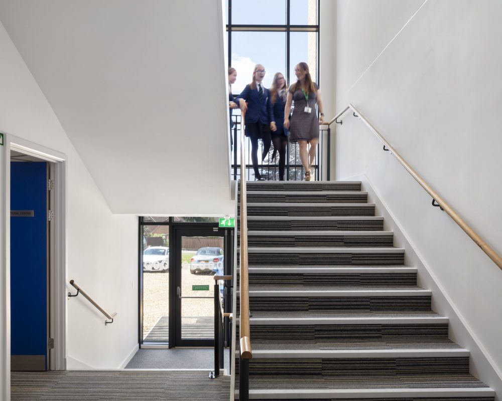 A group of pupils and a teacher walking downstairs