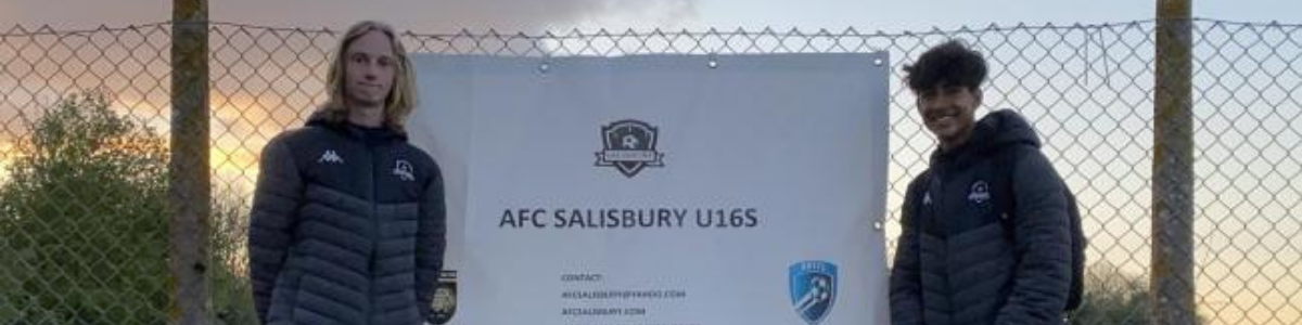 Boys standing in front of AFC Salisbury sign
