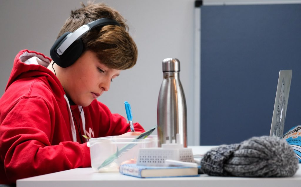 A boy wearing earphones working at a table