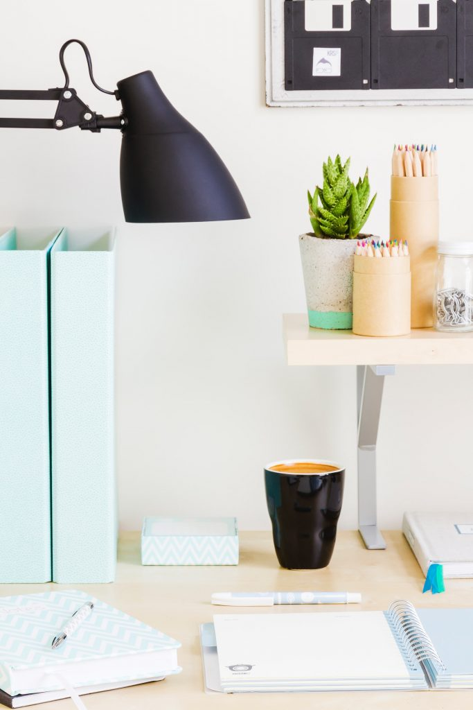 A desk with a notebook and a mug below a shelf with a potted plant and pencils